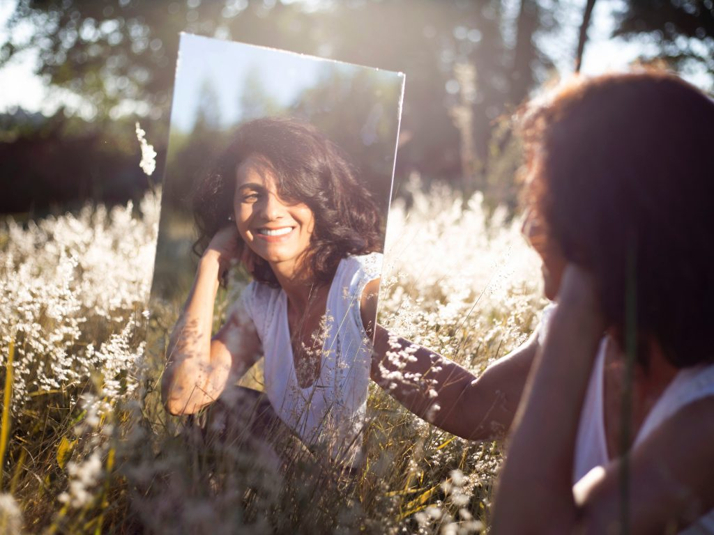 Woman in a field smiling in a mirror, showing how sustainable living in 2021 can feel great.